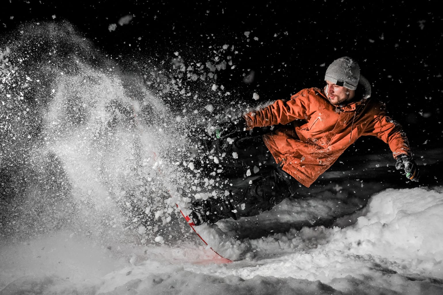 Young Snowboarder In Orange Sportswear And Jumping On The Board